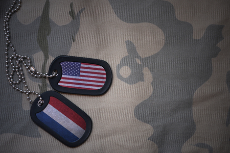 anti terrorist: army blank, dog tag with flag of united states of america and netherlands on the khaki texture background. military concept Stock Photo