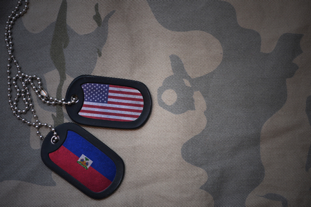 army blank, dog tag with flag of united states of america and haiti on the khaki texture background. military concept