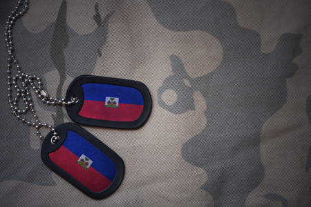 army blank, dog tag with flag of haiti on the khaki texture background. military concept