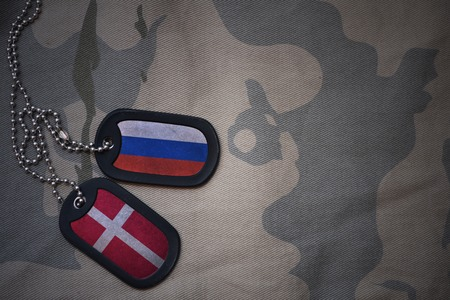 anti terrorist: army blank, dog tag with flag of russia and denmark on the khaki texture background. military concept Stock Photo