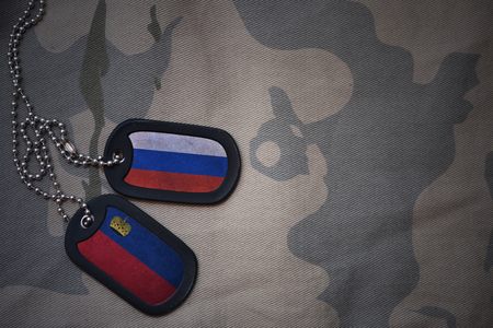 army blank, dog tag with flag of russia and liechtenstein on the khaki texture background. military concept Stock Photo