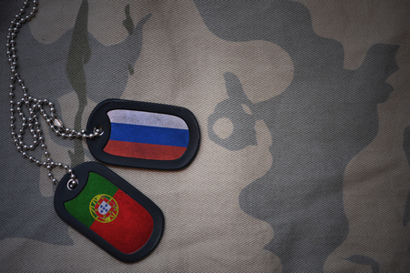 anti terrorist: army blank, dog tag with flag of russia and portugal on the khaki texture background. military concept