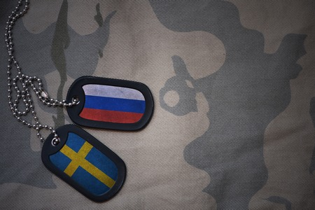 anti terrorist: army blank, dog tag with flag of russia and sweden on the khaki texture background. military concept
