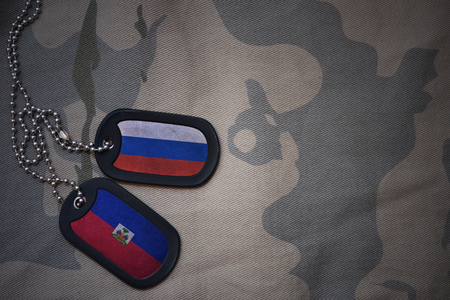 army blank, dog tag with flag of russia and haiti on the khaki texture background. military concept Stock Photo
