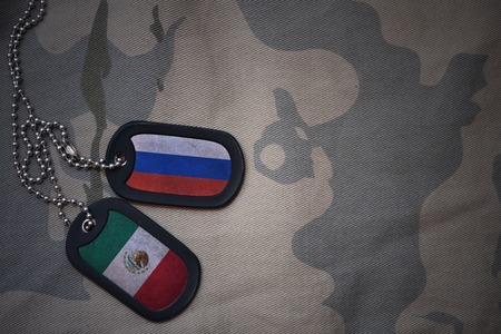 anti terrorist: army blank, dog tag with flag of russia and mexico on the khaki texture background. military concept