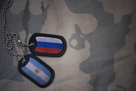 anti terrorist: army blank, dog tag with flag of russia and argentina on the khaki texture background. military concept