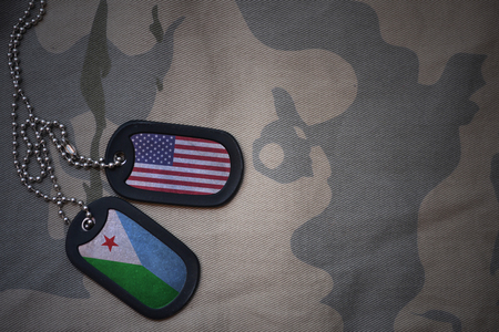 anti terrorist: army blank, dog tag with flag of united states of america and djibouti on the khaki texture background. military concept Stock Photo