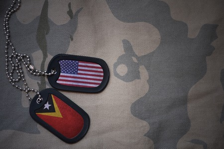 anti terrorist: army blank, dog tag with flag of united states of america and east timor on the khaki texture background. military concept Stock Photo