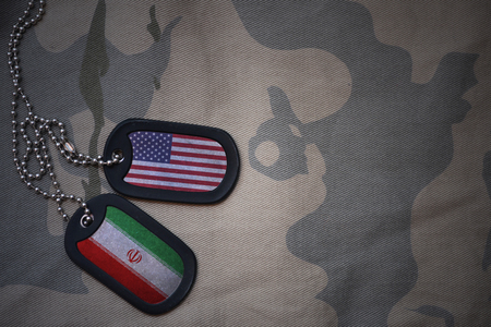 anti terrorist: army blank, dog tag with flag of united states of america and iran on the khaki texture background. military concept
