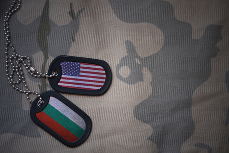 anti terrorist: army blank, dog tag with flag of united states of america and bulgaria on the khaki texture background. military concept