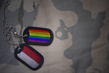 army blank, dog tag with flag of indonesia and gay rainbow flag on the khaki texture background. military concept