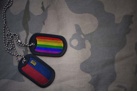 army blank, dog tag with flag of liechtenstein and gay rainbow flag on the khaki texture background. military concept