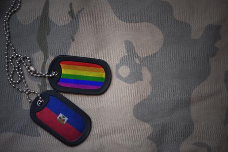 prince of peace: army blank, dog tag with flag of haiti and gay rainbow flag on the khaki texture background. military concept