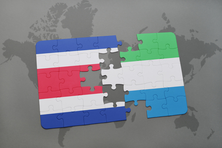 puzzle with the national flag of costa rica and sierra leone on a world map background. 3D illustration Stock Photo