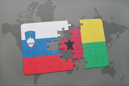 puzzle with the national flag of slovenia and guinea bissau on a world map background. 3D illustration