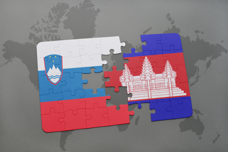 puzzle with the national flag of slovenia and cambodia on a world map background. 3D illustration Stock Photo