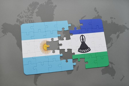 puzzle with the national flag of argentina and lesotho on a world map background. 3D illustration Stock Photo