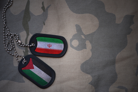 army blank, dog tag with flag of iran and palestine on the khaki texture background. military concept