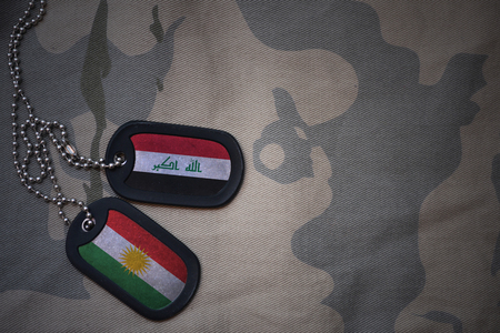 army blank, dog tag with flag of iraq and kurdistan on the khaki texture background. military concept