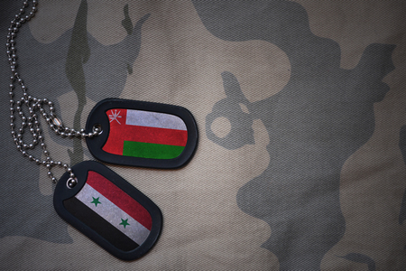 oman background: army blank, dog tag with flag of oman and syria on the khaki texture background. military concept