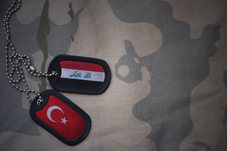iraqi: army blank, dog tag with flag of iraq and turkey on the khaki texture background. military concept