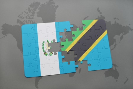 puzzle with the national flag of guatemala and tanzania on a world map background. 3D illustration Stock Photo