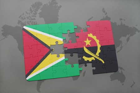 puzzle with the national flag of guyana and angola on a world map background. 3D illustration
