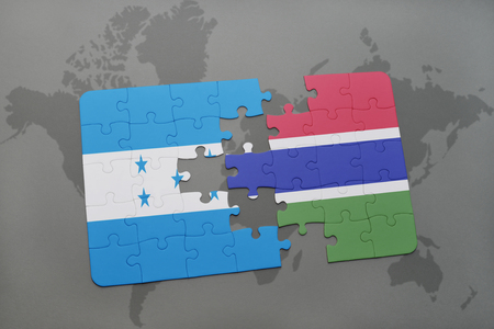 grey background texture: puzzle with the national flag of honduras and gambia on a world map background. 3D illustration Stock Photo