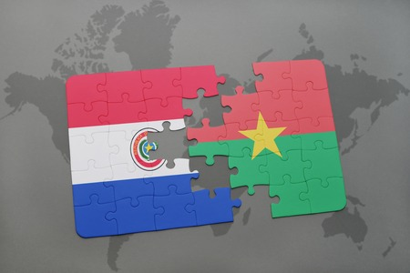 puzzle with the national flag of paraguay and burkina faso on a world map background. 3D illustration