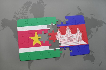 puzzle with the national flag of suriname and cambodia on a world map background. 3D illustration Stock Photo