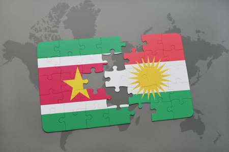 puzzle with the national flag of suriname and kurdistan on a world map background. 3D illustration Stock Photo