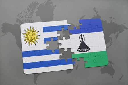 puzzle with the national flag of uruguay and lesotho on a world map background. 3D illustration