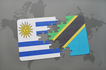 puzzle with the national flag of uruguay and tanzania on a world map background. 3D illustration