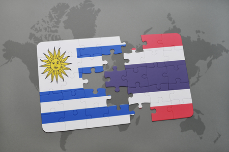 puzzle with the national flag of uruguay and thailand on a world map background. 3D illustration Stock Photo