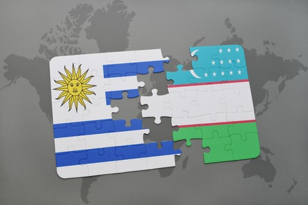 puzzle with the national flag of uruguay and uzbekistan on a world map background. 3D illustration Stock Photo