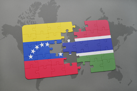 puzzle with the national flag of venezuela and gambia on a world map background. 3D illustration