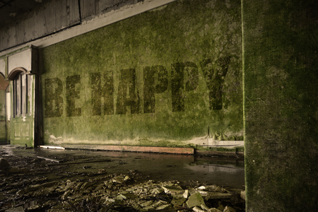 dirtiness: text be happy on the dirty old wall in an abandoned ruined house Stock Photo