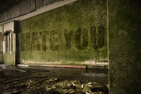 text hate you on the dirty old wall in an abandoned ruined house Stock Photo