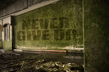 junky: text never give up on the dirty old wall in an abandoned ruined house