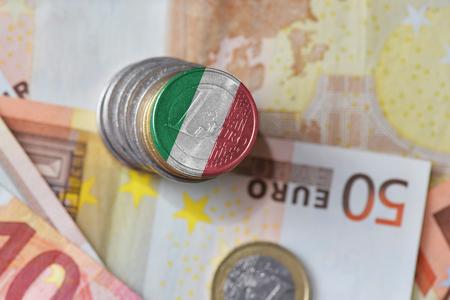 ユーロ硬貨はユーロのお金紙幣の背景にイタリアの国旗。財務の概念