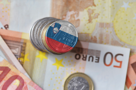 euro coin with national flag of slovenia on the euro money banknotes background. finance concept