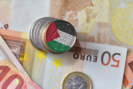 euro coin with national flag of palestine on the euro money banknotes background. finance concept