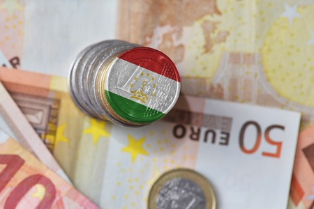 mideast: euro coin with national flag of tajikistan on the euro money banknotes background. finance concept