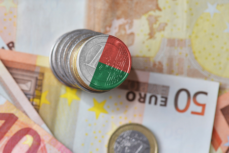euro coin with national flag of madagascar on the euro money banknotes background. finance concept
