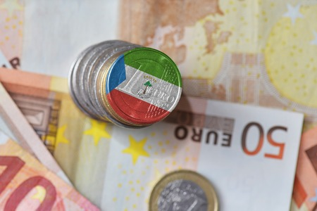 euro coin with national flag of equatorial guinea on the euro money banknotes background. finance concept