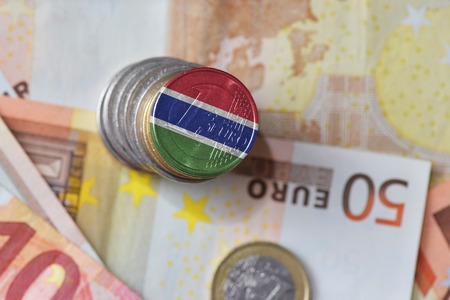 euro coin with national flag of gambia on the euro money banknotes background. finance concept
