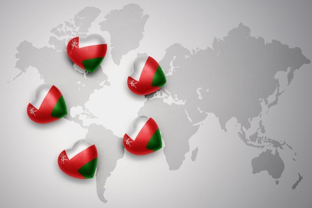 five hearts with national flag of oman on a world map background..concept.3D illustration Stock Photo