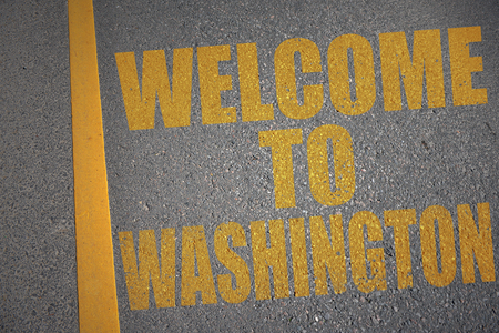asphalt road with text welcome to washington near yellow line. concept