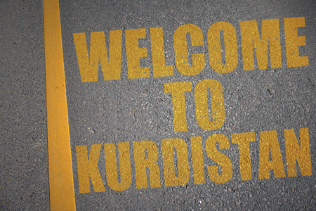 asphalt road with text welcome to kurdistan near yellow line. concept
