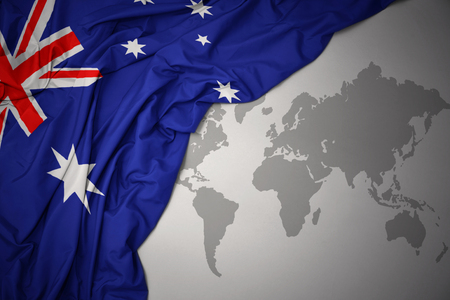 waving colorful national flag of australia on a gray world map background.